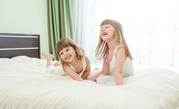 two small children playing on mattress